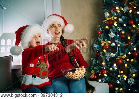 A Young Mother And Her Daughter In Santa Hats Watch Movies At Home On Christmas Day Pointing At The