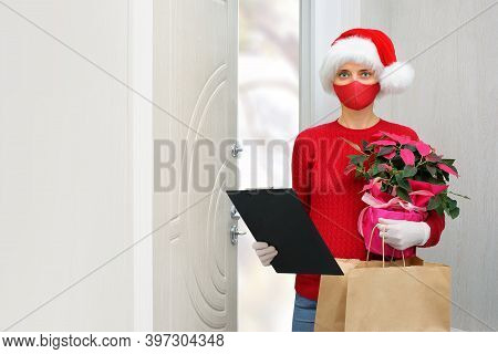 Home Shopping Delivery A Woman Wearing A Santa Hat, Gloves And A Protective Mask Delivers Packages D