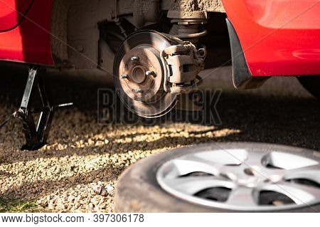 The Rear Hub Of A Car Without A Wheel With Sun Glare. Removed Wheel In The Foreground. The Concept O