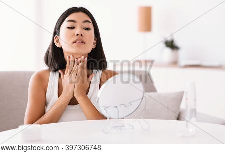 Facelift And Skin Care Concept. Portrait Of Beautiul Asian Woman Massaging Her Neck Sitting In Front