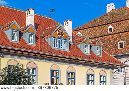 Roofs With Windows And Facade For Houses, Typical Architecture Of The Old City. The Eyes Are Baroque