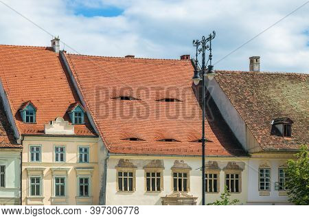 Roofs With Windows Like Eyes, Typical Architecture Of Sibiu, Transylvania, Romania. The Eyes Are Bar