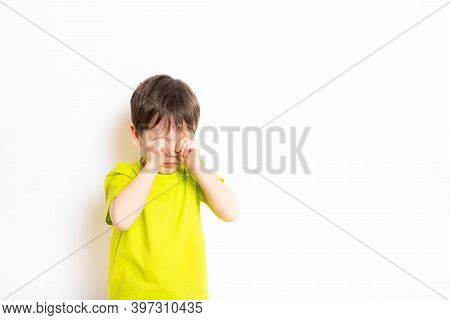 A Boy On A White Background Rubs His Eyes With His Hands . The Child Wants To Sleep . Article About