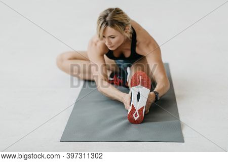 Modern Training With Gadget Indoor During Covid-19 Lockdown. Muscular Mature Lady In Sports Uniform