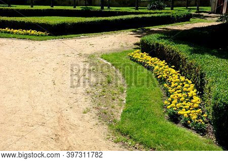 Bright Threshing Gravel Road With A Border Of Granite Cubes, Flowerbeds With Orange Yellow Flowers C