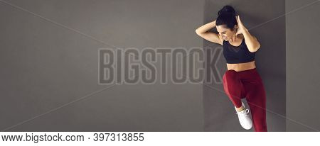 Gray Banner With Happy Fit Woman Doing Abs Exercise On Sports Mat During Workout At The Gym