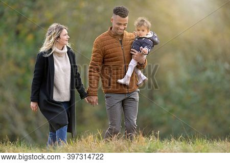 Young family walking together outside in countryside