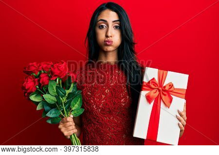 Beautiful hispanic woman holding anniversary gift and roses bouquet puffing cheeks with funny face. mouth inflated with air, catching air.