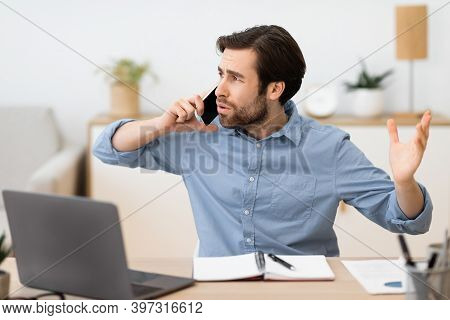 Angry Businessman Calling By Phone Having Problems Working At Laptop Sitting At Workplace In Modern