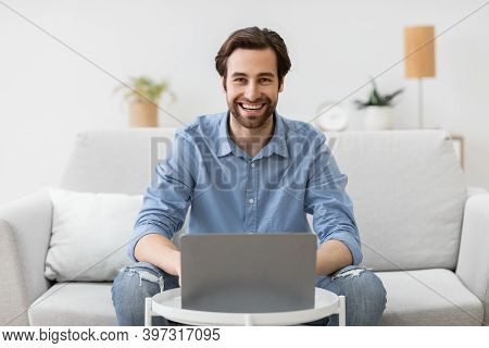 Happy Man At Laptop Computer Works Online And Smiles To Camera Sitting On Couch At Home. Successful