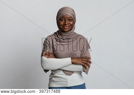 Portrait Of Confident Black Muslim Woman In Hijab Posing With Folded Arms Over Light Background, Bea