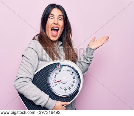 Young beautiful brunette sporty woman controlling weight using weighting machine celebrating achievement with happy smile and winner expression with raised hand