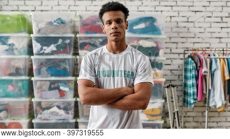 Cheerful Guy Looking At Camera, Posing With Arms Crossed In Front Of Rack And Boxes Full Of Clothes,
