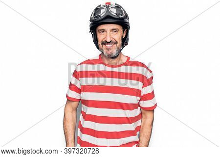 Middle age handsome motorcyclist man wearing moto helmet over isolated white background with a happy and cool smile on face. Lucky person.