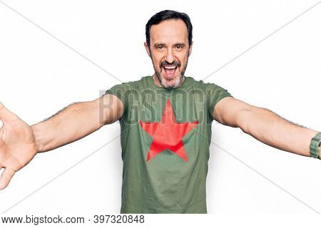 Middle age handsome man wearing t-shirt with revolutionary red star over white background looking at the camera smiling with open arms for hug. Cheerful expression embracing happiness.
