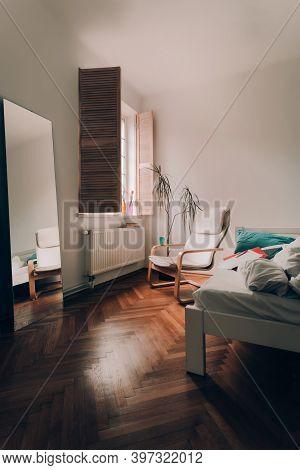 Cozy Corner In The Bedroom. Window With Wooden Shutters. Flowerpot. Modern Chair In Front Of Window