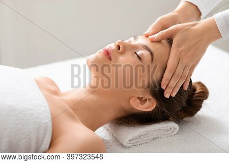 Acupressure Face Massage For Attractive Young Woman At Thai Spa Salon, Side View. Spa Attendant Maki