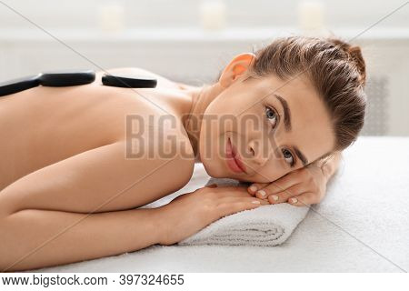 Beautiful Young Woman Resting During Hot Stone Massage At Spa Salon, Laying On Massage Table With Bl