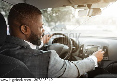 African American Businessman Turning On Music In Car Before Moving. Cheerful Black Businessman Pushi