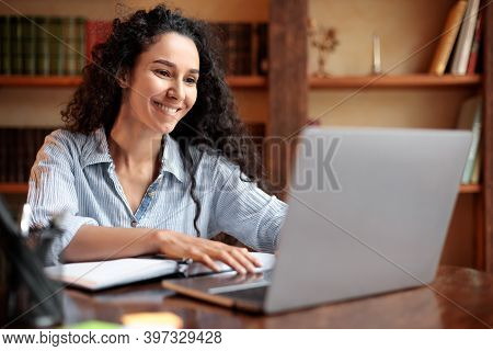 Home Office. Portrait Of Smiling Young Lady Sitting At Desk With Notebook, Using Laptop Computer And