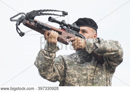 The Army Soldier In Military Uniform Is Aiming And Shooting A Crossbow Weapon.