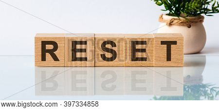 Wooden Blocks With The Text: Reset. The Text Is Written In Black Letters And Is Reflected In The Mir