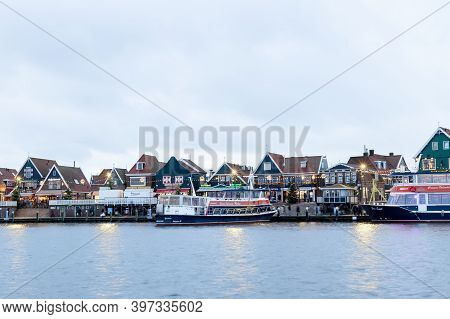 Volendam, Netherlands - December 24, 2019: Dutch Harbor With City Views, Boats, Christmas Decoration