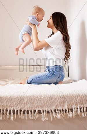 Mother And Baby In Bed. Young Mom Playing With Her Newborn Son. Child And Parent Together At Home. F