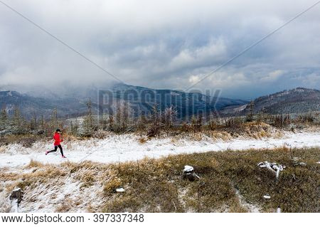 The View From The Drone On Girl Running In The Mountains In A Red Sweatshirt. The Beginning Of Winte