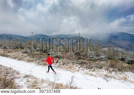 Drone View Of A Female Runner On A Trail In The Winter Mountains In The Snow.