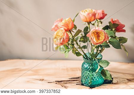 Rustic Bouquet Of Roses In Vase On Table In Sunlight.