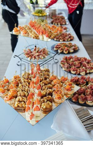 Sandwiches, Canapes And Cakes On The Festive Table. A Wide Variety Of Snacks