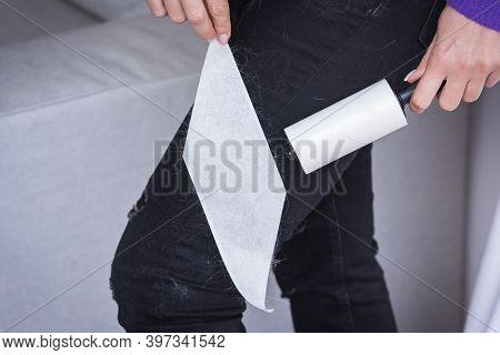 Close Up Of Woman Hand With Clothes Roller, Lint Roller Or Sticky Roller Removing Animal Hairs And F