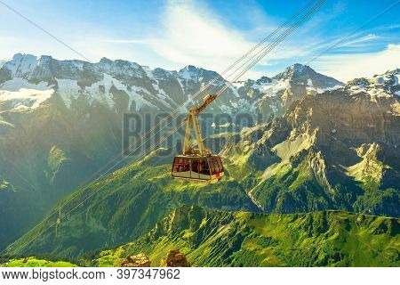 Cable Car From Murren To Birg And Schilthorn Summit Above Cliffs, Rocky Mountains And Valleys With L