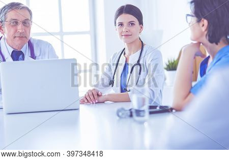 Serious Medical Team Using A Laptop In A Bright Consulting Room