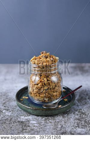 Crunchy Honey Homemade Granola With Nuts, Berries, Chocolate In A Glass Jar On A Gray Concrete Backg