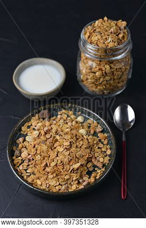 Crunchy Honey Homemade Granola With Nuts, Berries, Chocolate In A Glass Jar Served With Plant Yoghur
