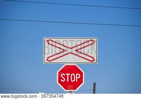 Level Crossing Sign, Called Crossbuck, Saltire Or Saint Andrews Cross, Standing On A Road Which Cros