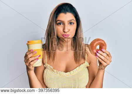Beautiful brunette woman eating doughnut and drinking coffee puffing cheeks with funny face. mouth inflated with air, catching air.