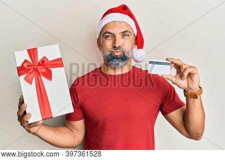 Middle age handsome man wearing chrismast hat holding gift and credit card puffing cheeks with funny face. mouth inflated with air, catching air.
