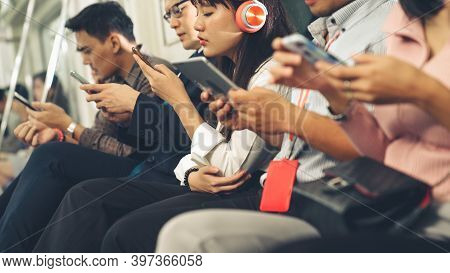 Young People Using Mobile Phone In Public Underground Train . Urban City Lifestyle And Commuting In