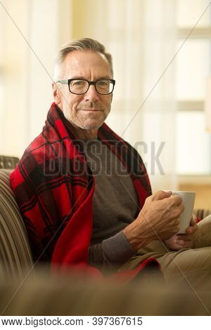 Mature Man Sitting On A Sofa Drinking Coffee.