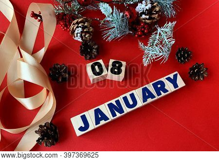 January 8 On Wooden Cubes.near Fir Branches, Cones, Ribbon, Gift Box On A Red Background.beginning O