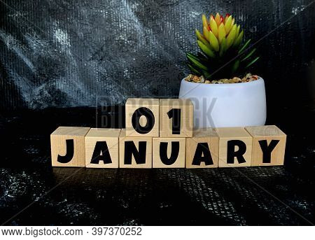 January 1 On A Black Background On Wooden Cubes .next To It Is A Pot With A Flower .calendar For Jan