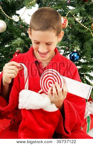 Cute little boy opens his stocking on Christmas morning.