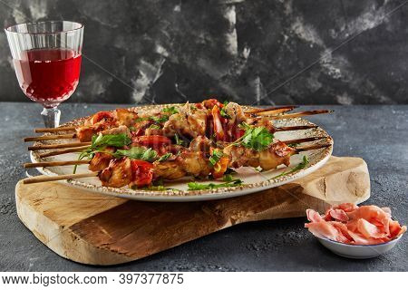 Japanese Style Yakitori Shashlik On A Wooden Board With A Glass Of Red Wine And Ginger. Copy Space F