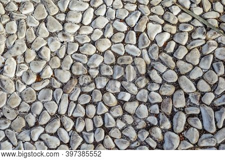 Texture Of White Sea Pebbles Cobbled On The Sidewalk, Close-up. Real Pattern Of Floor Paved With Nat
