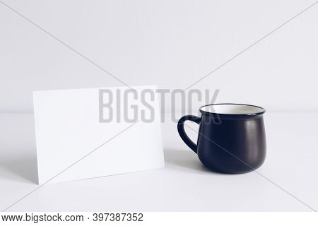 Enamel Black Mug And Horizontal Postcard On White Table Background Mockup. Boho Style Classic Stock