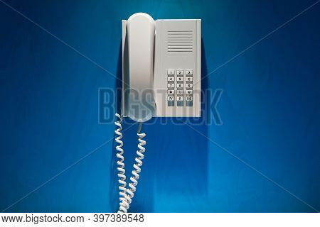Phone mounted on the wall of a blue booth