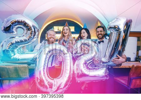 Party people women and men celebrating new years eve 2021 by holding up the numbers